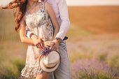 pic of windy weather  - Young beautiful sensual couple kissing outdoors in windy weather in the summer on a lavender field - JPG