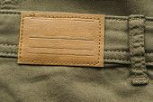 picture of khakis  - Blank leather label on khaki cloth as a background - JPG