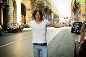 foto of daring  - Man Wearing White T Shirt with Open Arms Standing in Street and Facing Camera