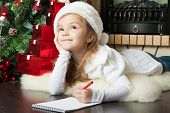 stock photo of christmas hat  - Funny girl in Santa hat writes letter to Santa near christmas tree - JPG