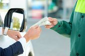 image of dispenser  - Businessman give money dispensers filled car on gas station - JPG