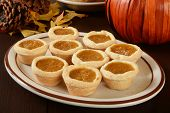 picture of pumpkin pie  - A plate of pumpkin pies on a holiday table - JPG