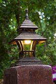 stock photo of roof-light  - small old wooden roof lamp and lighting on old wood in garden - JPG