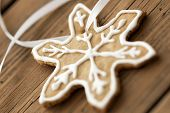 stock photo of ginger bread  - White Decorated Ginger Bread Star Cookie on white Ribbon as Macro as Background on Wood