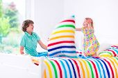 stock photo of pillow-fight  - Two children having a pillow fight with feathers in the air jumping laughing and giggling in a white bedroom with colorful bedding.