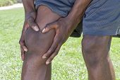 pic of knee-cap  - Closeup of knee and leg of lean African American male athlete clutching injured knee with fingers around the patella on green lawn outdoors - JPG