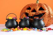 stock photo of cauldron  - Happy Halloween candy in trick or treat carry cauldrons with pumpkin on orange background - JPG