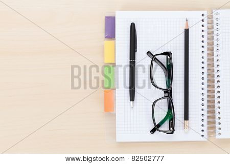Office table with glasses over notepad, pen and pencil. Top view with copy space