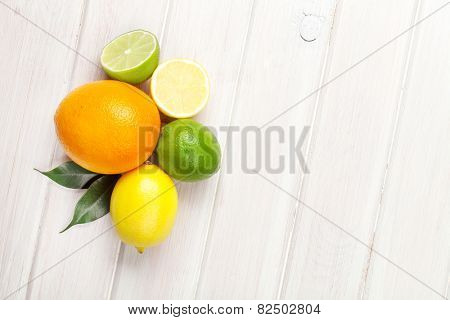 Citrus fruits. Oranges, limes and lemons. Top view over wooden table background with copy space