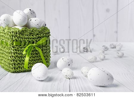Easter eggs in a green basket on a white table