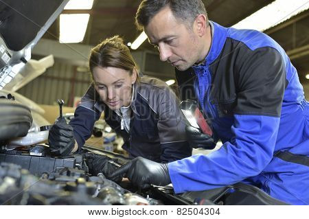 Mechanics instructor teaching woman in apprenticeship