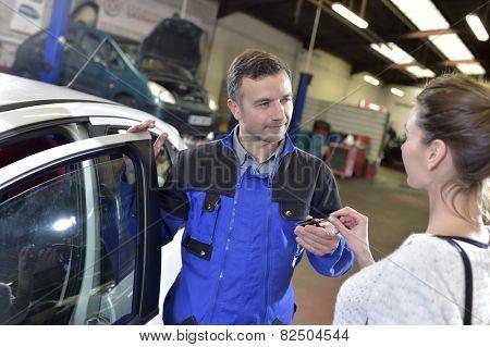 Auto repair mechanic giving car keys back to customer