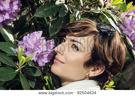 Young Caucasian Woman Sniffs Purple Flowers In The Park