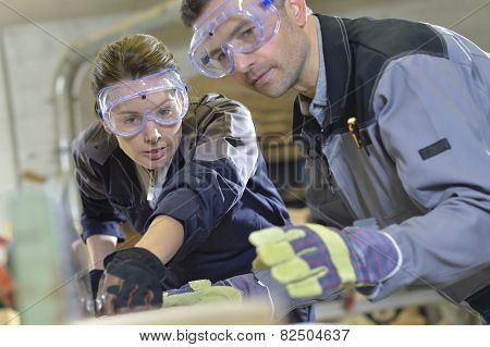 Instructor showing trainee how to use sawing machine