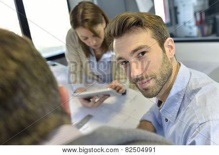 Portrait of architect amongst group in meeting