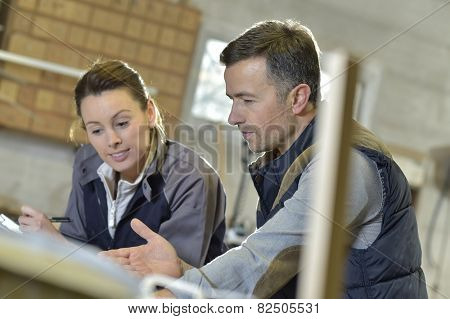 Woman with instructor in carpentry workshop