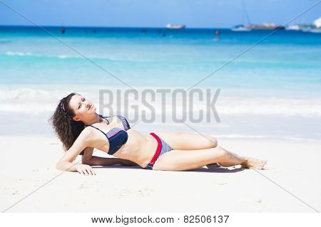Beautiful young brunette is laying near the tropical sea on the white beach at Barbados