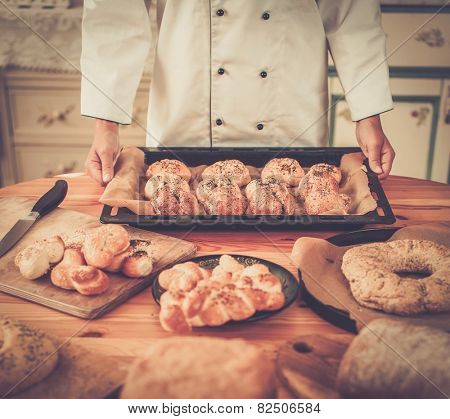 Cook hands holding baking tray with homemade baked goods
