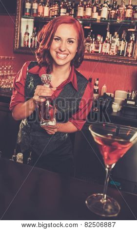 Beautiful redhead barmaid with bottle behind bar counter