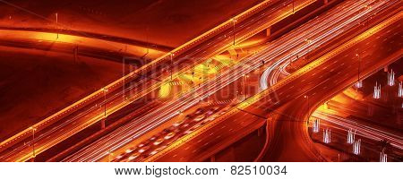 Night roads panoramic background, bird eye view on illuminated highway, modern motorway in Dubai city, UAE