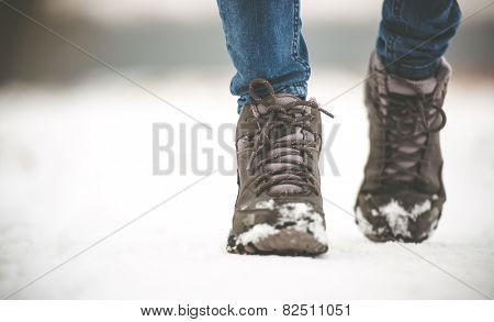 girl in winter boots walking on snowy road
