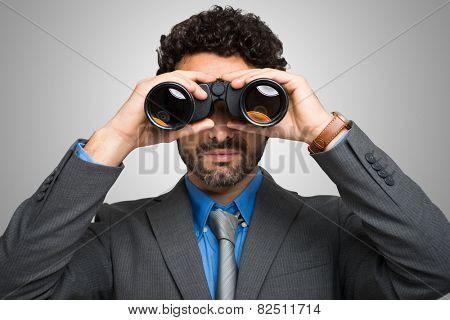 Businessman watching through binoculars