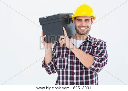 Portrait of happy male repairman carrying toolbox on shoulder over white background