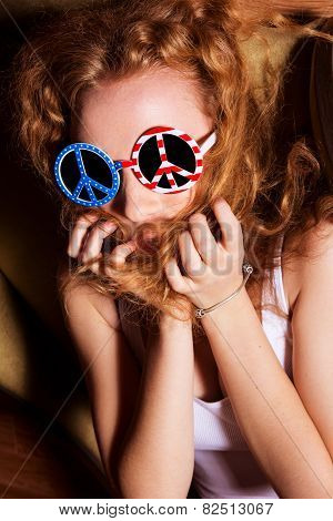Young Girl With Curly Hair Wearing Sunglasses With The American Flag And A Sign Of Peace