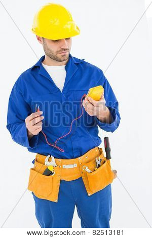 Repairman examining multimeter while standing against white background