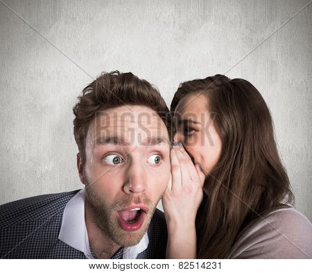 Woman whispering secret into friends ear against weathered surface