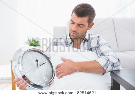 Anxious man beside clock with a pillow at home in the living room