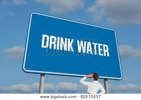 The word drink water and businesswoman scratching her head against sky