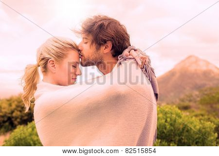 Cute affectionate couple standing outside wrapped in blanket on a chilly day