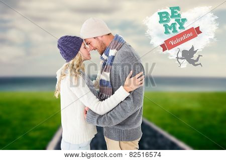 Attractive couple in winter fashion hugging against cloud heart