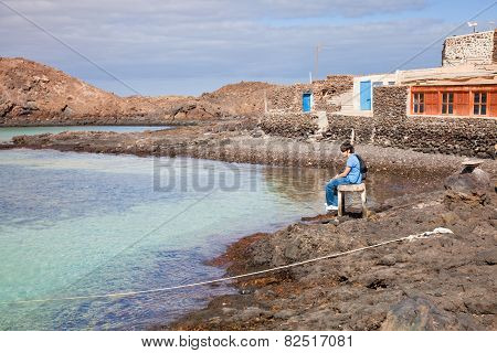 Two Brothers Sitting In The Small Port Of Isla De Lobos,  Canary Islands