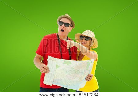 Happy tourist couple using map against green vignette