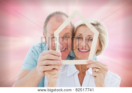 Happy older couple holding house shape against digitally generated pink girly design