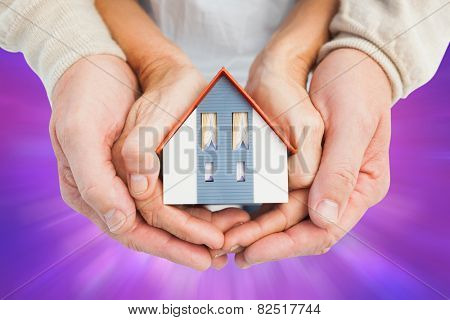 Couple holding small model house in hands against purple abstract light spot design