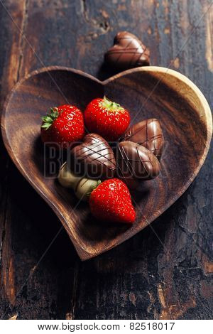 heart shape plate with strawberries and chocolate on wooden table - Valentine's day and love concept