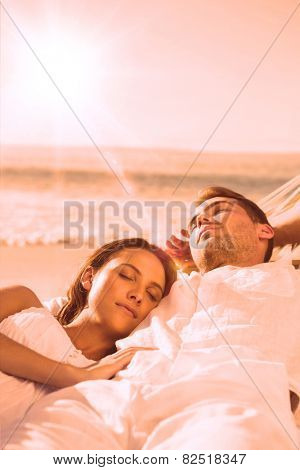 Peaceful couple sleeping in a hammock on the beach