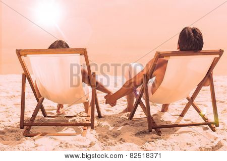 Couple lying on deck chairs holding their hands on beach