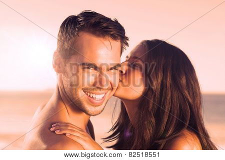 Attractive woman on the beach kissing her boyfriend on the cheek