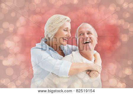 Happy mature couple smiling at each other against light glowing dots design pattern