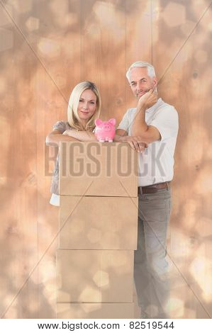 Happy couple leaning on pile of moving boxes with piggy bank against light glowing dots design pattern