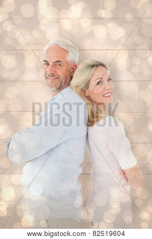 Smiling couple standing leaning backs together against light glowing dots design pattern