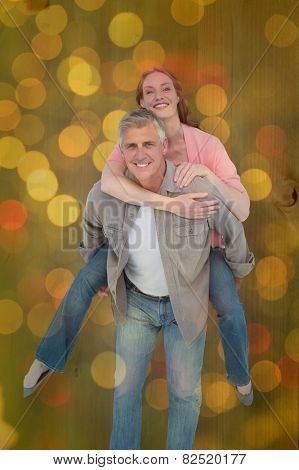 Casual couple having fun together against close up of christmas lights