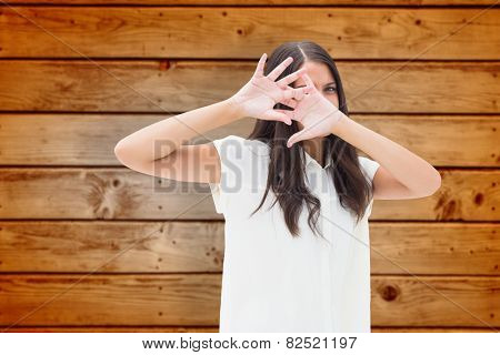 Fearful brunette covering her face against wooden planks background
