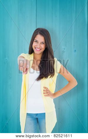 Happy casual woman pointing to camera against wooden planks background