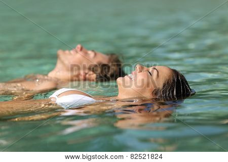 Couple Of Tourists Swimming In The Sea Of A Tropical Resort
