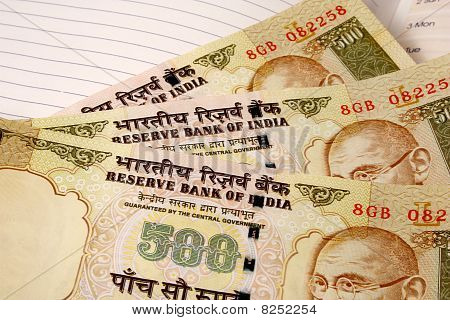 three 500 rupee indian currency notes on a ruled paper notebook